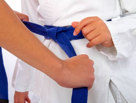 adult woman helps tighten the blue belt to the little girl karate