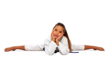little karate girl in a white kimono and a blue belt sits for a workout in sports twine