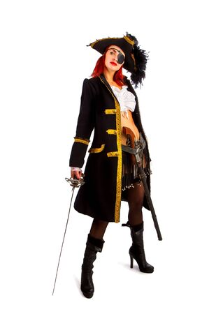 sexy girl in a pirate costume and a cocked hat stands armed with a sword on a white background in high heels. Stockfoto