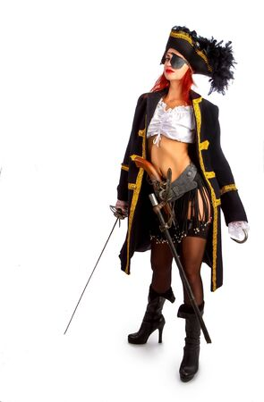 sexy girl in a pirate costume and a cocked hat stands armed with a sword on a white background in high heels. With a hook instead of the left hand Stockfoto