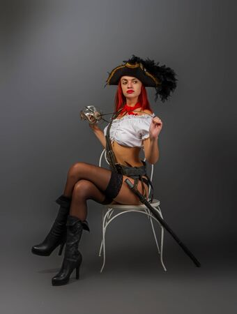 Bright armed girl the pirate captain in a cocked hat is standing in underwear and stockings and a short white blouse is sitting on a chair.