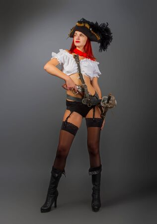 Bright armed sexy girl the pirate captain in a cocked hat stands in underwear and stockings and a short white blouse on a dark background