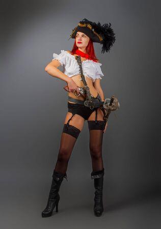 Chica armada brillante, el capitán pirata con un sombrero de tres picos se encuentra en ropa interior y medias y una blusa blanca corta sobre un fondo oscuro