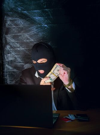 a bandit in a mask of a balaclava using a laptop does not fair profit on the Internet Zdjęcie Seryjne