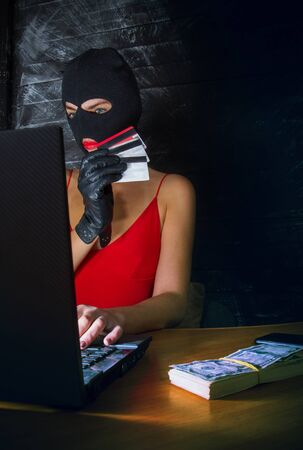 young girl in a sexy red dress and a balaclava mask sits at a laptop and makes an honest profit on the Internet