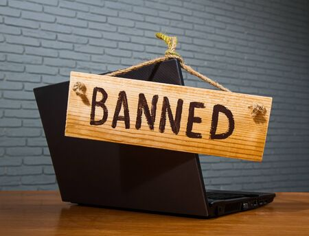 turned off laptop with a wooden sign that says banned