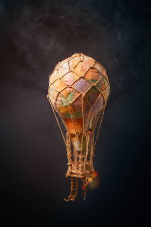 fabulous steam airship with a patchwork balloon flying among the clouds on a dark background. Not real