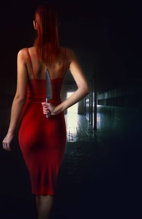 Sexy young red-haired girl in a bright red dress is walking along an empty dark corridor holding a knife in his hand hiding it behind his back. Imagens