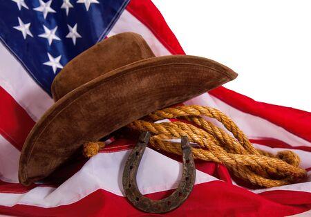 cappello da cowboy, lazo e ferro di cavallo sdraiato sulla bandiera degli Stati Uniti isolato su sfondo bianco Archivio Fotografico