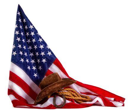 cowboy hat, lasso and horseshoe lying on the usa flag isolated on white background