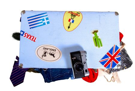 old suitcase full of things to relax with stickers from visited places ready for travel isolated on white background