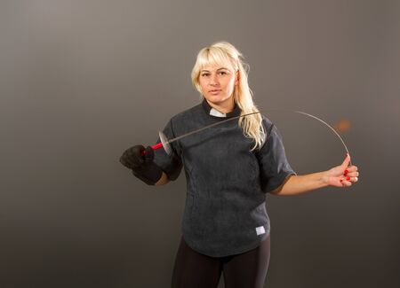 Young blonde girl in a fencing coaching dark uniform stands with a rapier on a gray background
