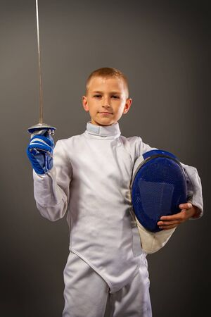 Little boy in a white protective suit fencing mask and with a rapier exercises in fencing on a dark background Archivio Fotografico