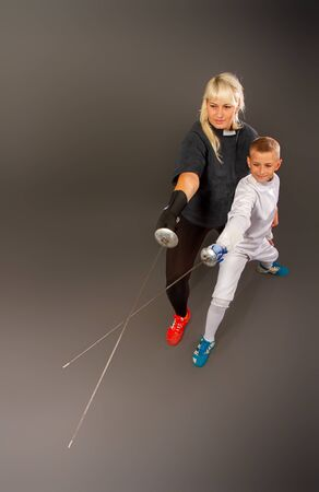 Young blonde girl in a dark coaching outfit and a little boy in a white sports outfit practicing rapier fencing on a gray background