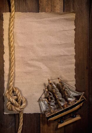 old sheet of parchment or paper lying on wooden boards and a coarse rope pulled into a nautical knot forming a frame
