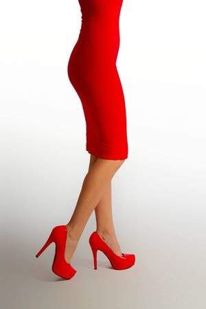 slim female legs in bright red high-heeled shoes and a red dress on a light background