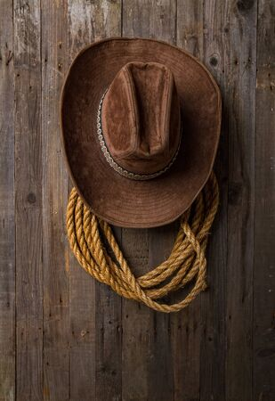 old classic wide-brimmed cowboy brown hat and lasso hanging on a rough wooden wall