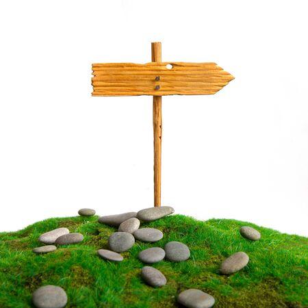empty homemade wooden pointer towards the establishment of an artificial grass among the rocks Standard-Bild