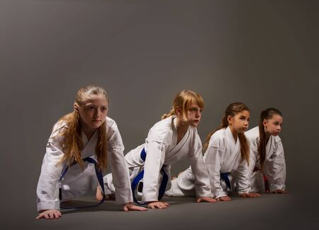 several little girls in karate uniforms push up on their hands from the floor in training