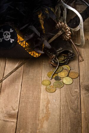 pirate hat, sword and wallet with little things on a rustic wooden table