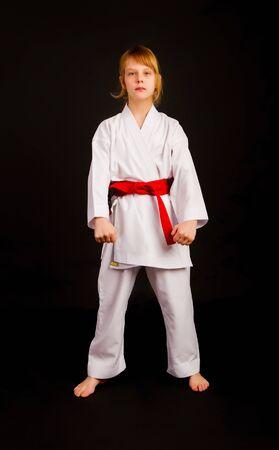 Dziewczynka w sportowym kimonie i czerwonym pasie wykonuje ćwiczenia kata na ciemnym tle