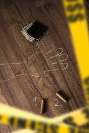 Crime scene fenced with yellow police tapes with a silhouette of the victim painted on the floor with chalk and brass sleeves from a hunting rifle