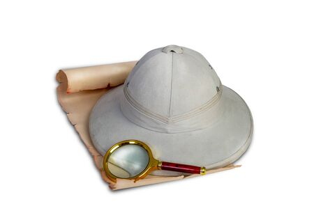 Tropical travelers cork helmet lying on an old scroll or map next to a magnifying glass isolated on white background 版權商用圖片