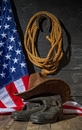 classic cowboy wide-brimmed brown brown lasso hat made of coarse rope and riding boots on a dark wooden background next to the US flag