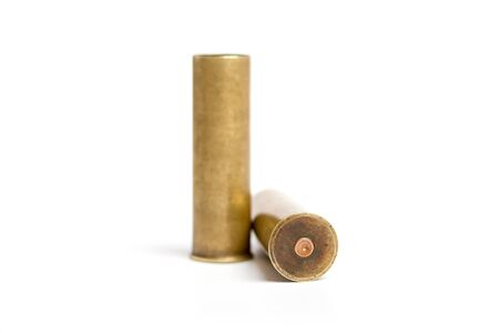 two old brass shot cartridges of a twelfth caliber hunting rifle on a white background