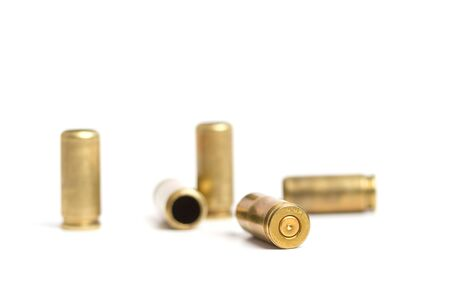 several used brass shells from a nine mm pistol on a white background Stock Photo
