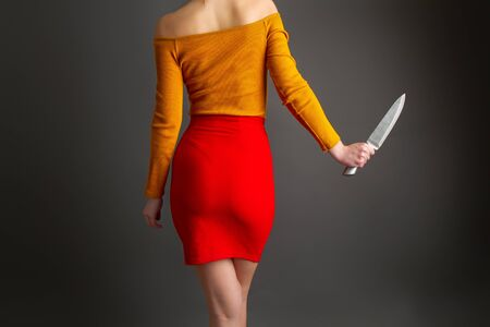 A young girl in a bright skirt and blouse holds in her hands a large steel kitchen knife on a dark background