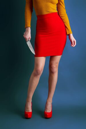 Une jeune fille vêtue d'une jupe et d'un chemisier brillants tient dans ses mains un grand couteau de cuisine en acier sur fond sombre