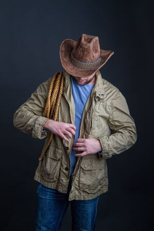 Cowboy in a wide-brimmed hat and jacket with a lasso on his shoulder posing on a dark background