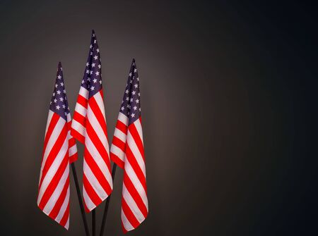 Three star-striped US flags on flagpoles on a dark background