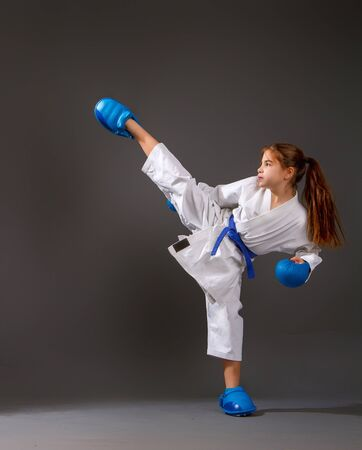 Little girl in a white kimono with a blue belt and equipment carries out blows on a dark background Archivio Fotografico