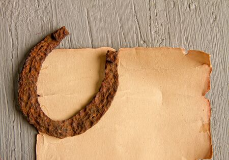 A very old rusty horse horseshoe a symbol of good luck lies on an empty paper scroll Stock Photo