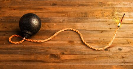 classic round black antique bomb with a long burning rope wick on a rough wooden background Imagens