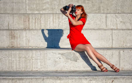 Young beautiful girl photographer in a bright red dress focuses on a model with a large digital camera Foto de archivo