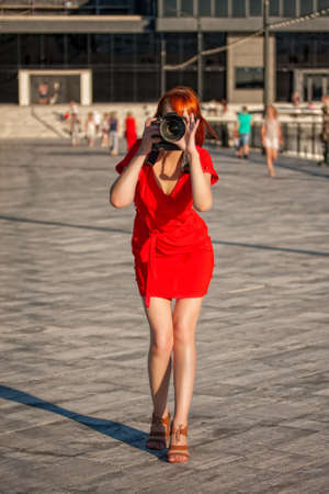 Young beautiful girl photographer in a bright red dress focuses on a model with a large digital camera Imagens