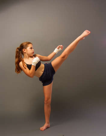 little girl in a sports tank top and shorts with hands wrapped in protective bandage is engaged in martial arts on a dark background