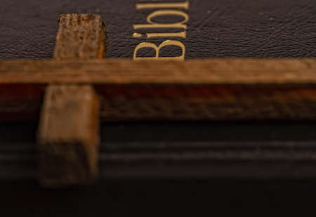 Old closed cover holy bible and simple wooden cross close up