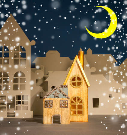 A street of cardboard and wood cut houses imitating a small cute European city on a dark blue background and snow 免版税图像