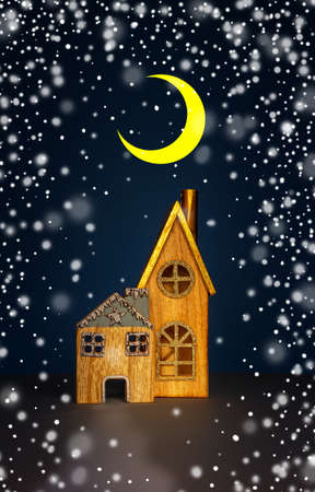 two cute wooden toy houses with windows and triangular roofs on a blue background and snow
