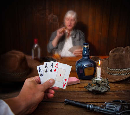 two people in the wild west play cards in the saloon with their revolvers and hats on the table
