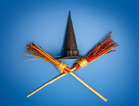 Classic witch black pointed hat and two crossed flying brooms