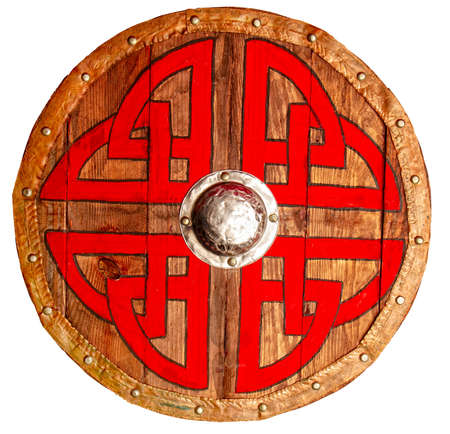 Viking round wooden brown shield decorated with a rough red-black pattern and metallic and copper protective elements