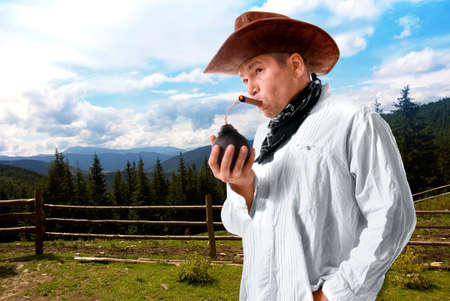 Adult male cowboy with wide-brimmed hat sets fire to a lighted cigar bomb on a ranch