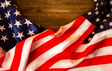 Two Stars and Stripes of the United States of America stacked on an old wooden background with a place for an inscription Foto de archivo