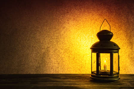 Lonely burning candle in an old lantern on a dark brown background Foto de archivo