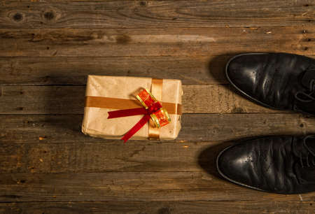 Conceptual photo - a gift wrapped with his own hand by a child for Father's Day next to rough men's shoes on a wooden floor.